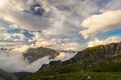 Ultima luce solare calda sulla valle alpina con i picchi di montagna d'ardore e le nuvole sceniche Alpi francesi italiane, destin Fotografie Stock