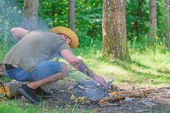Ultimate guide to bonfires. Arrange the woods twigs or wood sticks standing like a pyramid and place the leaves under. Man straw hat prepares bonfire in forest royalty free stock photos
