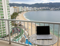 Ultimate Home office. Laptop on a table on a balcony overlooking a great view of Acapulco bay & beach Stock Images