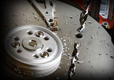 Ultimate solution. Close up on classic hard disk destroy by drill background stock photography