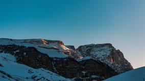 Ultimi raggi del sole snowly su un picco di montagna Fotografia Stock