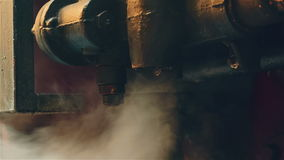 Ultra Close-up of an Industrial Engine Exhausting Steam. An ultra close-up shot of an old industrial locomotive engine expelling steam and dripping water stock video