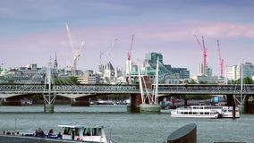 ULTRA HD 4k, real time, London skyline with boats and bridge on Thames river. London, UK- Circa 2015: London skyline and boats on Thames river in a sunny day stock footage