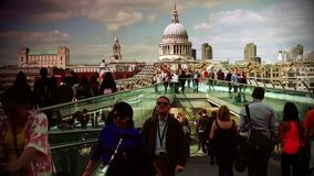 ULTRA HD 4k, real time, People walking over Millennium bridge with St. Paul iconic London Image. stock video footage