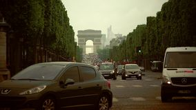 ULTRA HD 4K real time,Traffic drives along the Champs-Elysees. Paris, France - circa 2015: Traffic drives along the Champs-Elysees at sunset with the Arc de stock video