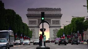 ULTRA HD 4K, real time, zooming; sunset with the Arc de Triomphe with traffic cars. Paris, France - circa 2015: Traffic drives along the Champs-Elysees at sunset stock video footage