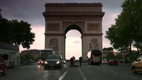 ULTRA HD 4K, real time, zooming; sunset with the Arc de Triomphe with traffic cars. Paris, France - circa 2015: Traffic drives along the Champs-Elysees at sunset stock footage