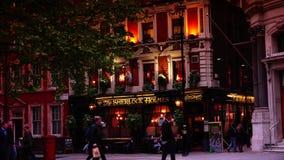 ULTRA HD 4k, tiempo real, gente tienen una bebida en el pub de Sherlock Holmes en Londres
