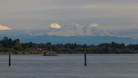 Time lapse of rolling clouds over snow covered Mt. Baker along Semiahmoo Bay in WA state stock video footage