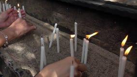 Ultra langzame motie - Kaarsen die voor workship bij kerk branden stock videobeelden