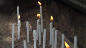 Ultra langzame motie - Kaarsen die voor workship bij kerk branden stock video