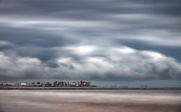 Ultra long exposure of skyscrappers near sea with clouds. Long shot ultra long exposure of skyscrappers near sea with stormy clouds royalty free stock image