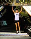 Ultra Marathoner, der springt, um Timer-Vorstand zu klopfen Stockbilder
