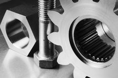 Ultra-modern mechanic menagerie. Cog, bolt and nut against aluminum Royalty Free Stock Photo