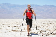 Ultra running man - trail runner in extreme race. Training for marathon. Fit male athlete running with trekking hiking poles in Death Valley, USA Royalty Free Stock Photo
