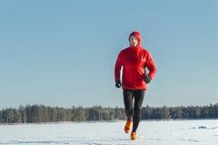 Ultra trascini il corridore che porta gli abiti sportivi protettivi rossi sull'inverno che si prepara all'aperto Fotografia Stock Libera da Diritti