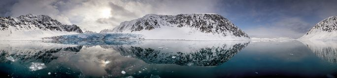 Ultra wide panorama of Kongsvegen glacier in Svalbard. Mirror reflection panorama of the blue glacial ice, mountains and clouds of Kongsvegen glacier, in royalty free stock photos