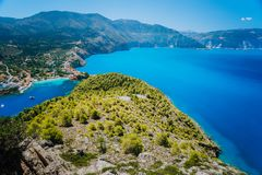 Ultra wide shot of Assos village in morning light, Kefalonia. Greece. Beautiful turquoise colored bay lagoon water. Surrounded by pine and cypress trees along royalty free stock photos