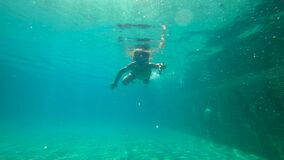 Ultrahd slowmotion underwater shot of a little boy learns how to swim in a pool. Toddler boy dives into pool. Ultrahd slowmotion underwater shot of a little boy stock video footage