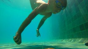 Ultrahd slowmotion underwater shot of a little boy learns how to swim in a pool. Toddler boy dives into pool and pulls. Stones from the bottom stock footage