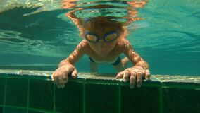 Ultrahd slowmotion underwater shot of a little boy throwing stones to the pool.  stock video