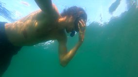 Ultrahd slowmotion underwater shot of a man snorkeling in sea at a troical island.  stock footage