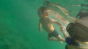 Ultrahd slowmotion underwater shot of a woman and her son sweaming and diving in a sea.  stock footage