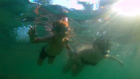 Ultrahd slowmotion underwater shot of a woman and her son sweaming and diving in a sea.  stock video