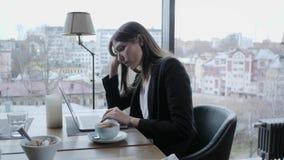 Ultrajado y reacciona seriamente Mujer joven que se sienta en cafeter?a en la tabla de madera En la tabla es el ordenador port?ti almacen de video