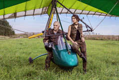 Ultralight airplane on the field. The pilot sits in an ultralight plane, standing next to a girl in military clothes Royalty Free Stock Photos