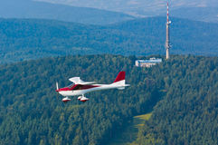 Ultralight airplane in flight over the forests Stock Photography