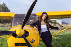 Ultralight airplane and laughing brunette. Yellow ultralight aircraft on green field and around the laughing girl Stock Photography