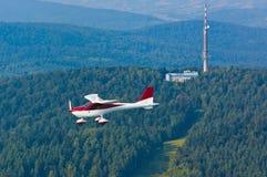 Ultralight flygplan i flykten över skogarna Arkivbild