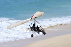 Ultralight Flying coming in for a landing on the beach. Ultralight pilot landing his aircraft on the beach royalty free stock images