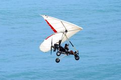 Ultralight Flying over the Ocean. Ultralight pilot flying his aircraft over the ocean royalty free stock image
