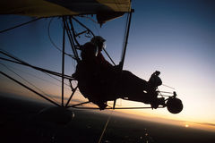 Ultralight silhouette 1. Two pilots fly in an ultralight plane Royalty Free Stock Photography