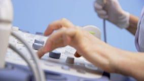 Ultraljudapparattangentbord, händer av den oigenkännliga doktorn som arbetar med ultraljuds- utrustning lager videofilmer