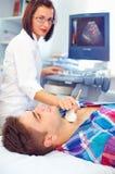 Ultraljudscanning av en sköldkörtel av mannen Arkivbild