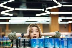Ultramarinos casuales jovenes de la cosecha de la mujer en un supermercado Foto de archivo