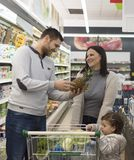 Ultramarinos de compra de la familia en el supermercado local foto de archivo libre de regalías