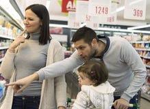 Ultramarinos de compra de la familia en el supermercado local imagen de archivo libre de regalías