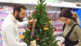Ultramarinos de compra de la familia feliz joven en el supermercado para la Navidad metrajes