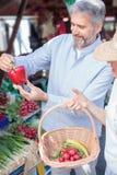 Ultramarinos que hacen compras de los pares maduros en un mercado orgánico local del aire abierto imagenes de archivo