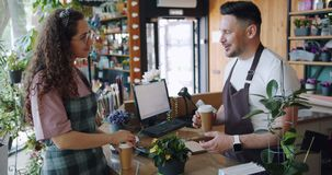 Ultrarapid av anställda för blommalager som talar diskutera växten som rymmer kaffe lager videofilmer