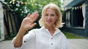 Ultrarapid av att le den vinkande handen för dam som välkomnar stående det fria i stad arkivfilmer