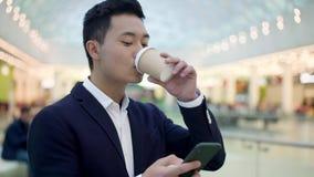 Ultrarapid av den asiatiska unga affärsmannen i dräkt som dricker kaffe som smsar på telefonen