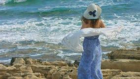 Ultrarapid av den attraktiva kvinnan i det hållande ögonen på havet för den långa klänningen vinkar på stenig kust lager videofilmer