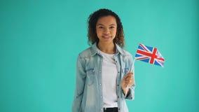 Ultrarapid av den gulliga afrikansk amerikandamen med brittiskt le f?r nationsflagga lager videofilmer