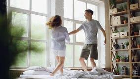 Ultrarapid av den gulliga pardansen på säng som hoppar och skrattar ha tillsammans gyckel på helgmorgon i trevligt ljus stock video