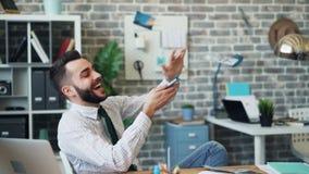 Ultrarapid av den lyckliga entrepereneuren som kastar kassa som i regeringsställning skrattar ha gyckel arkivfilmer